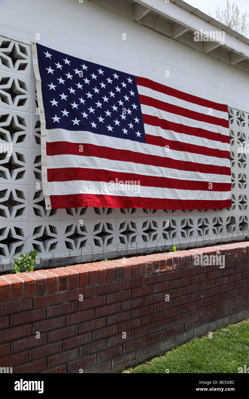 American flag hanging on side of home - Stock Image