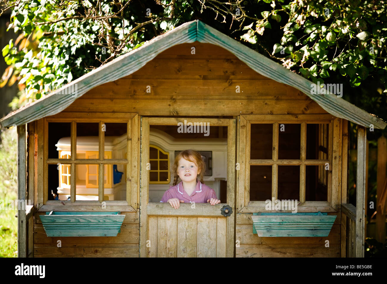 redhead girl in playhouse - Stock Image