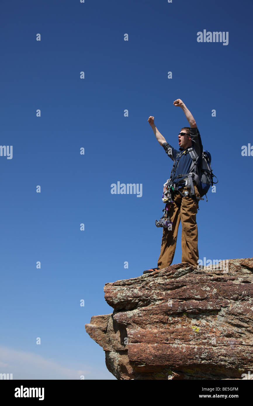 Climber celebrates on top of rock - Stock Image
