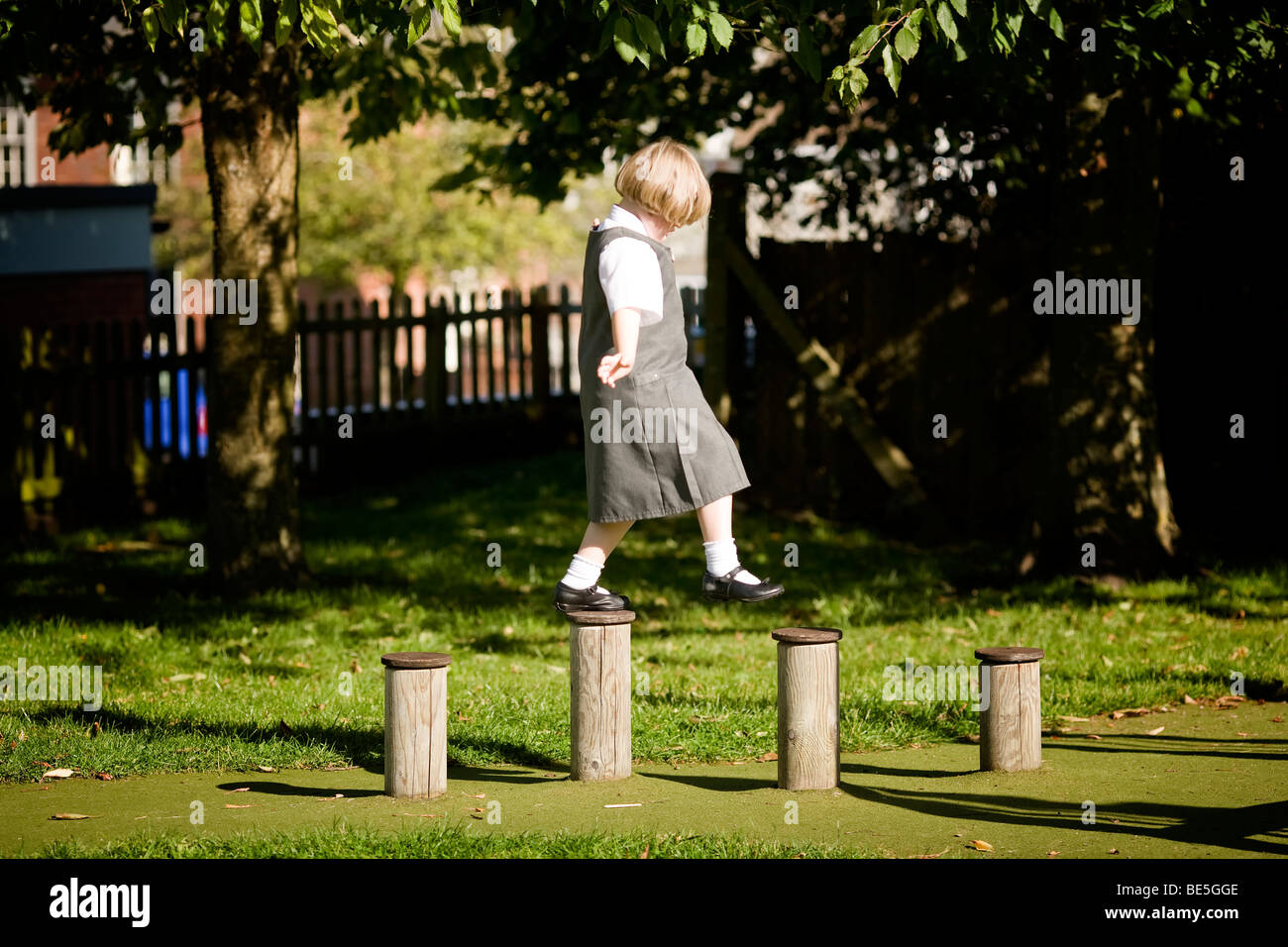 girl walking across obstacle course - Stock Image