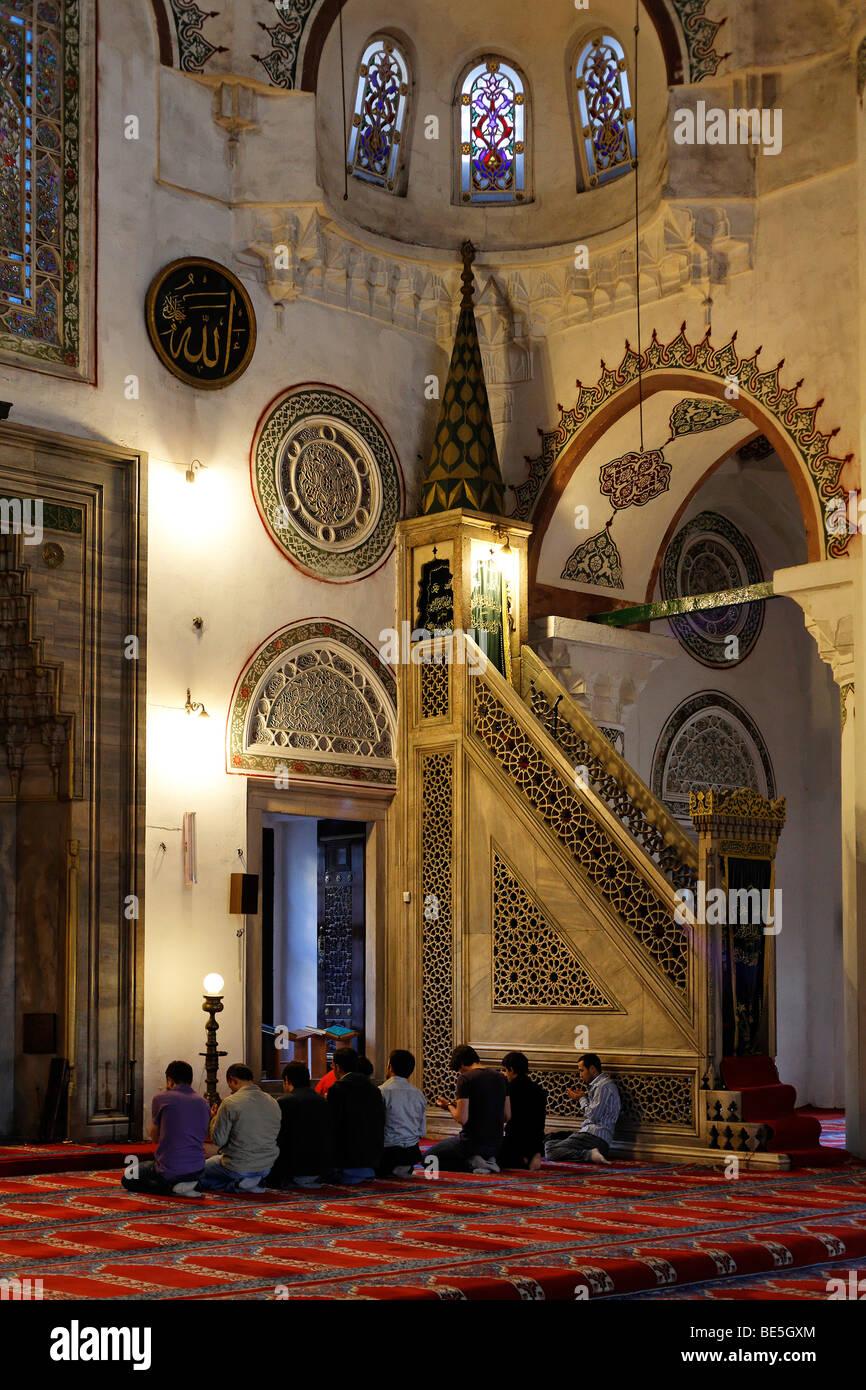 Young Muslim men pray in the Iskele, Mirimah Sultan Mosque, Ueskuedar, Istanbul, Turkey - Stock Image