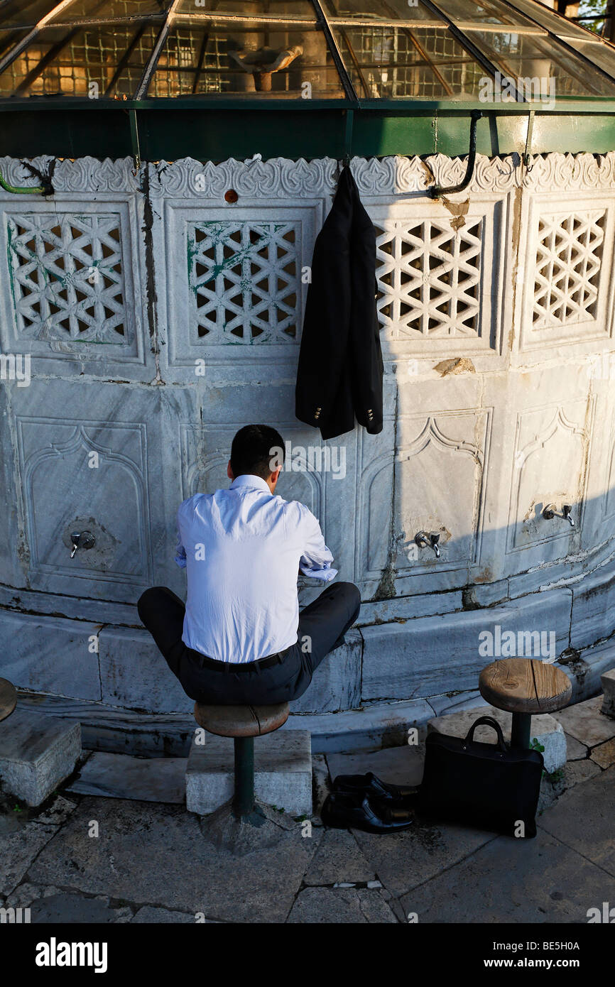 Muslim man in business clothes washes his feet in a purgation well, Sadirvan, Iskele, Mirimah Sultan Mosque, Ueskuedar, - Stock Image