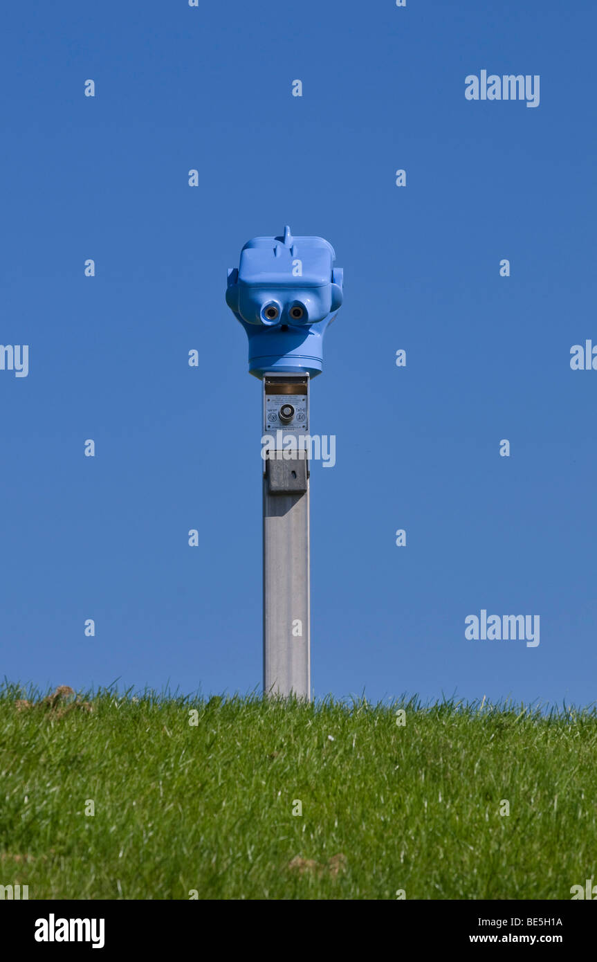 Blue coin-telescope, Euroskop on grass turf against a blue sky - Stock Image