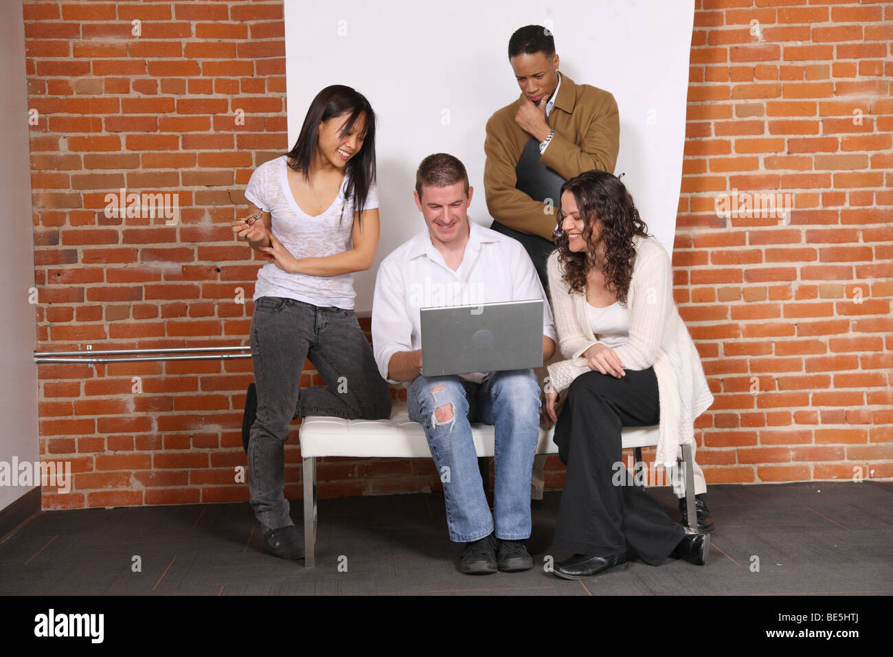 Group of young casual businesspeople look at laptop together - Stock Image