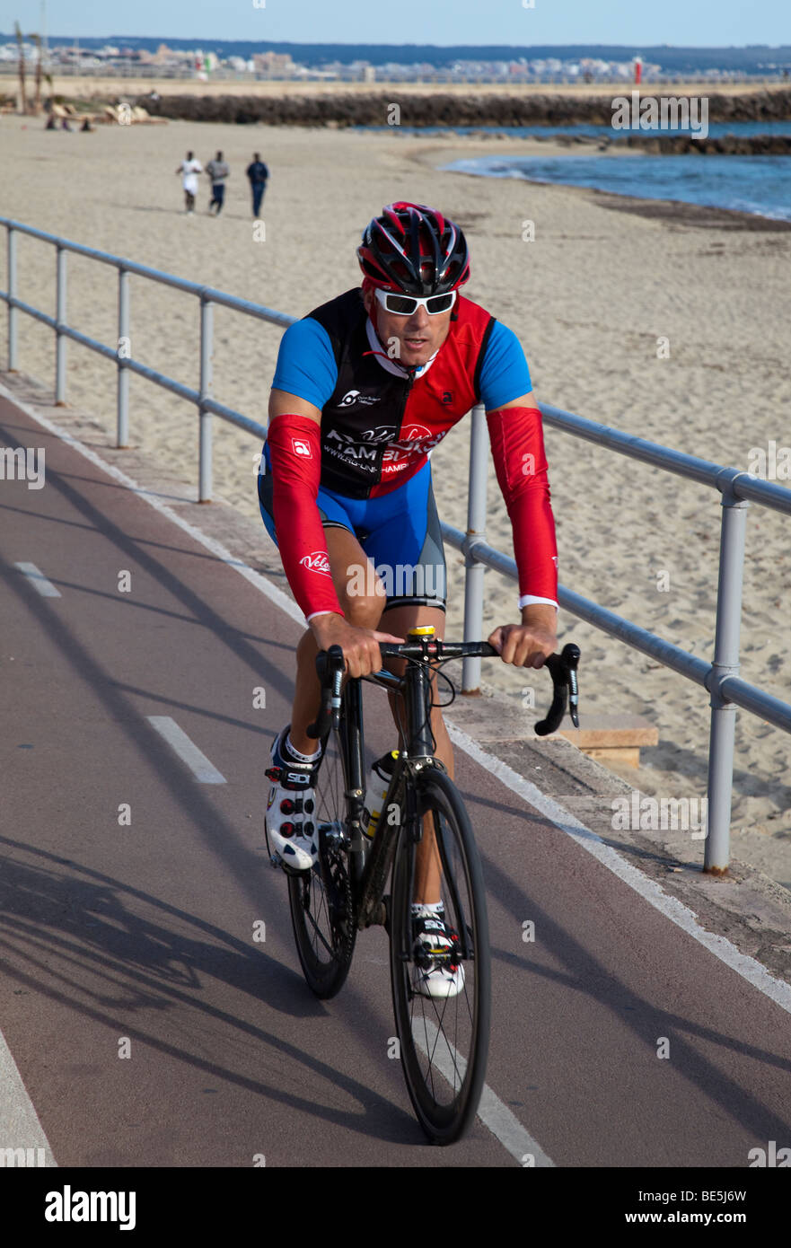 Man cycling on promenade in cycle lane with men running training on beach Palma Mallorca Spain - Stock Image