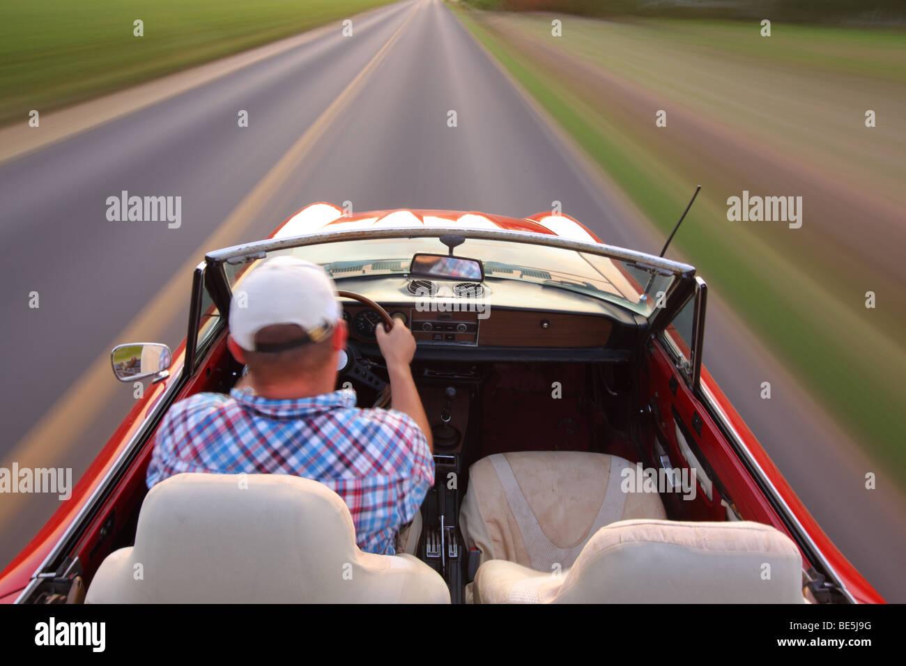 Blurred motion shot of man driving convertible - Stock Image