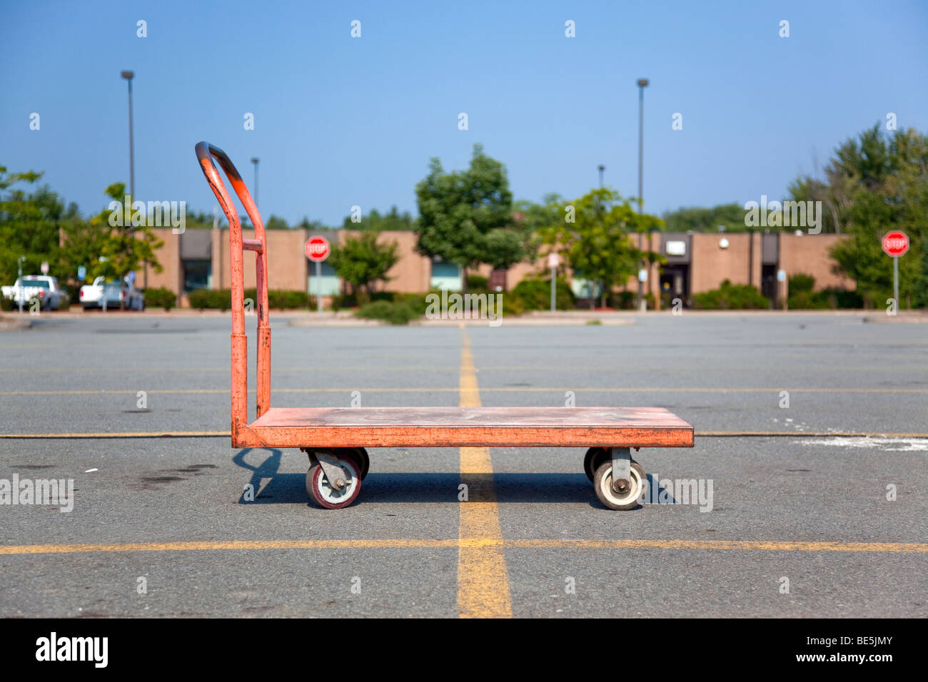 Orange flat bed cart at a store's parking lot with stop signs and building visible in the background - Stock Image