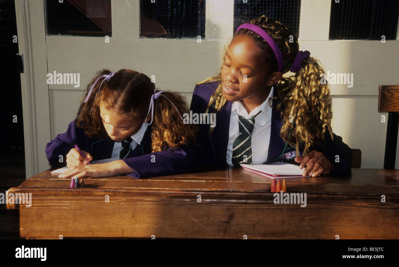 Two little girls in a classroom.  One girl is taking a sneaky peek her friend's work. - Stock Image