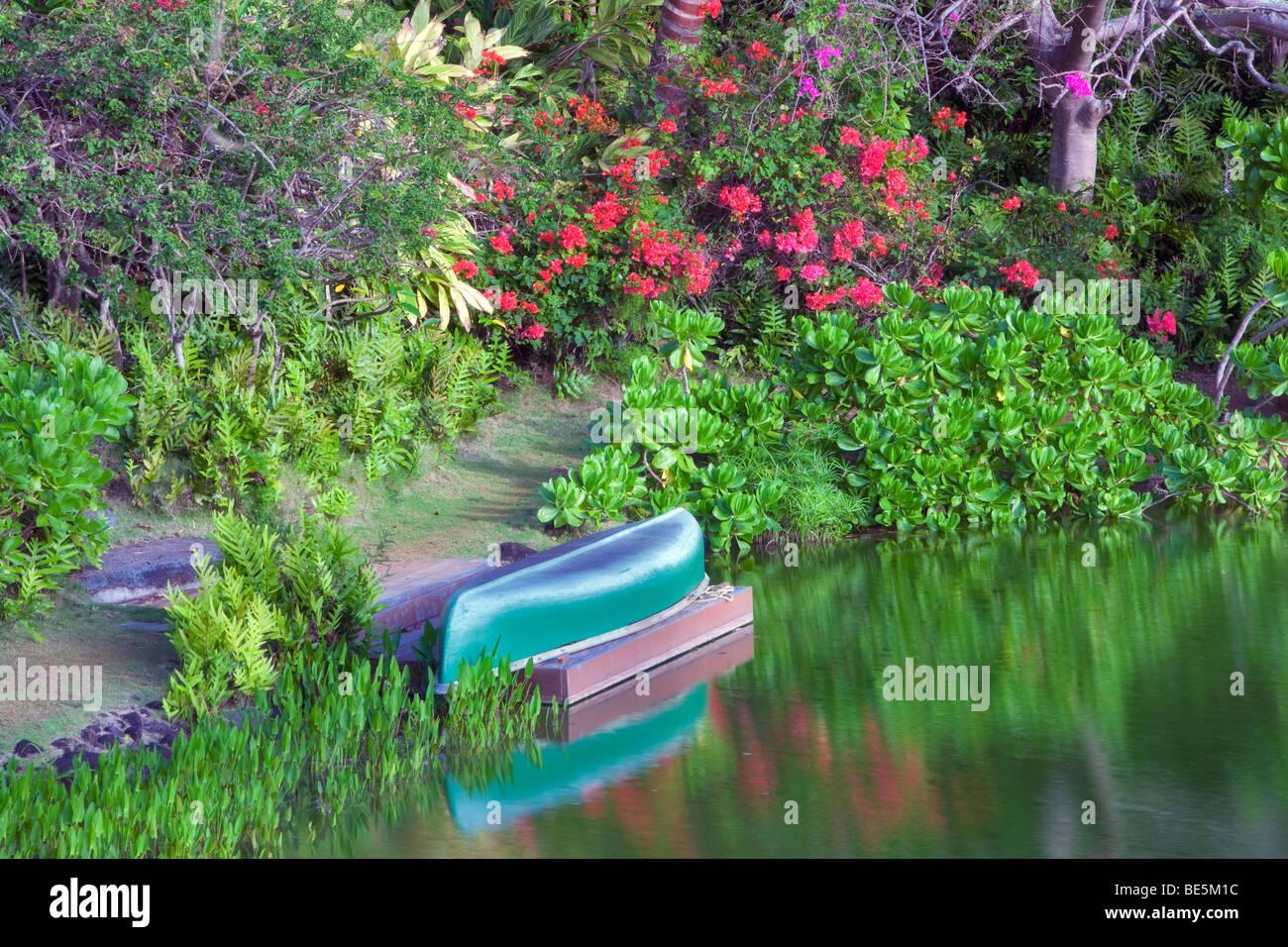 Pond with canoe and garden at Na Aina Kai Botanical Gardens. Kauai, Hawaii - Stock Image