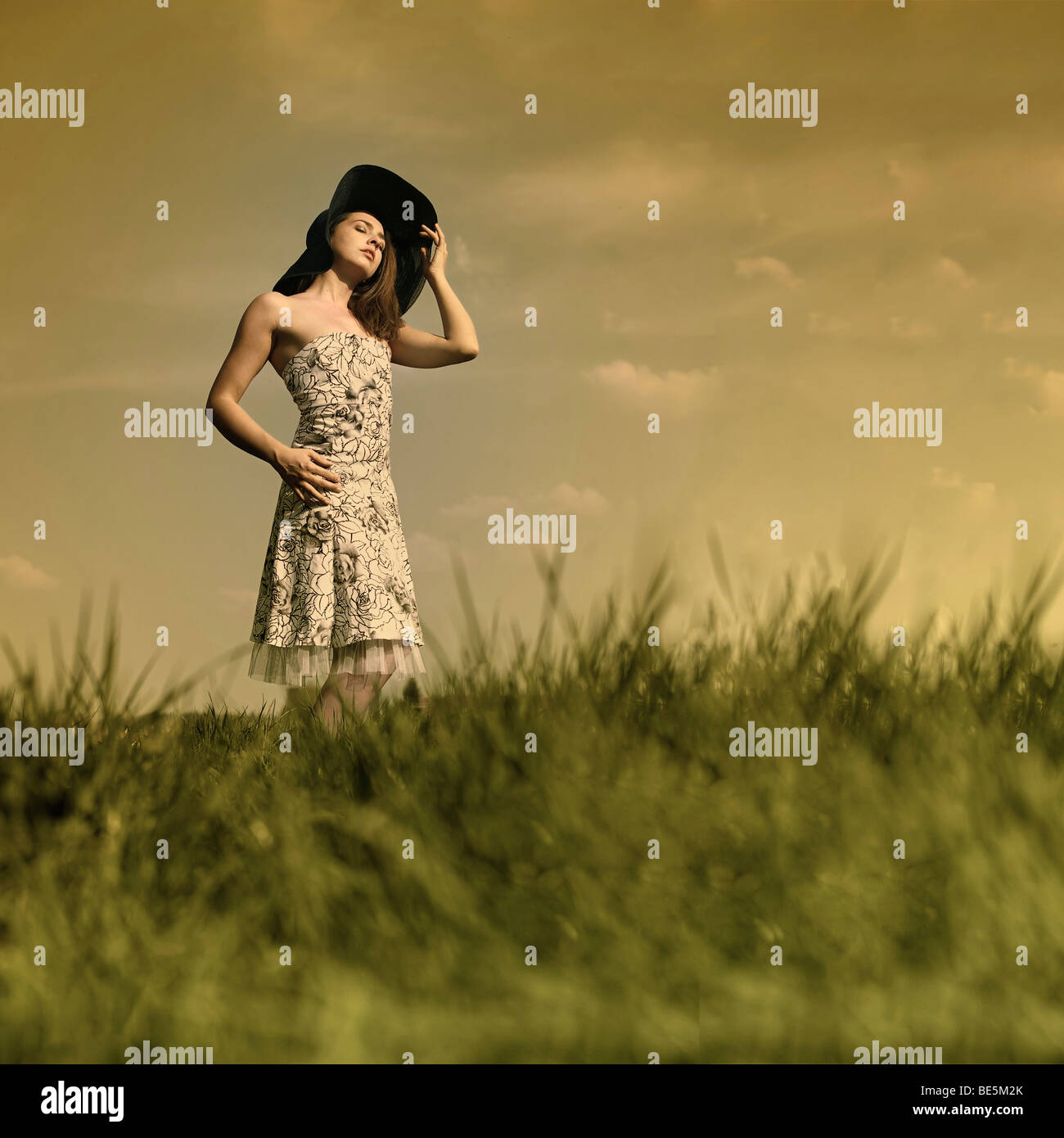 Young woman with a flowery summer dress and large hat is standing in a meadow and looking into the sun - Stock Image