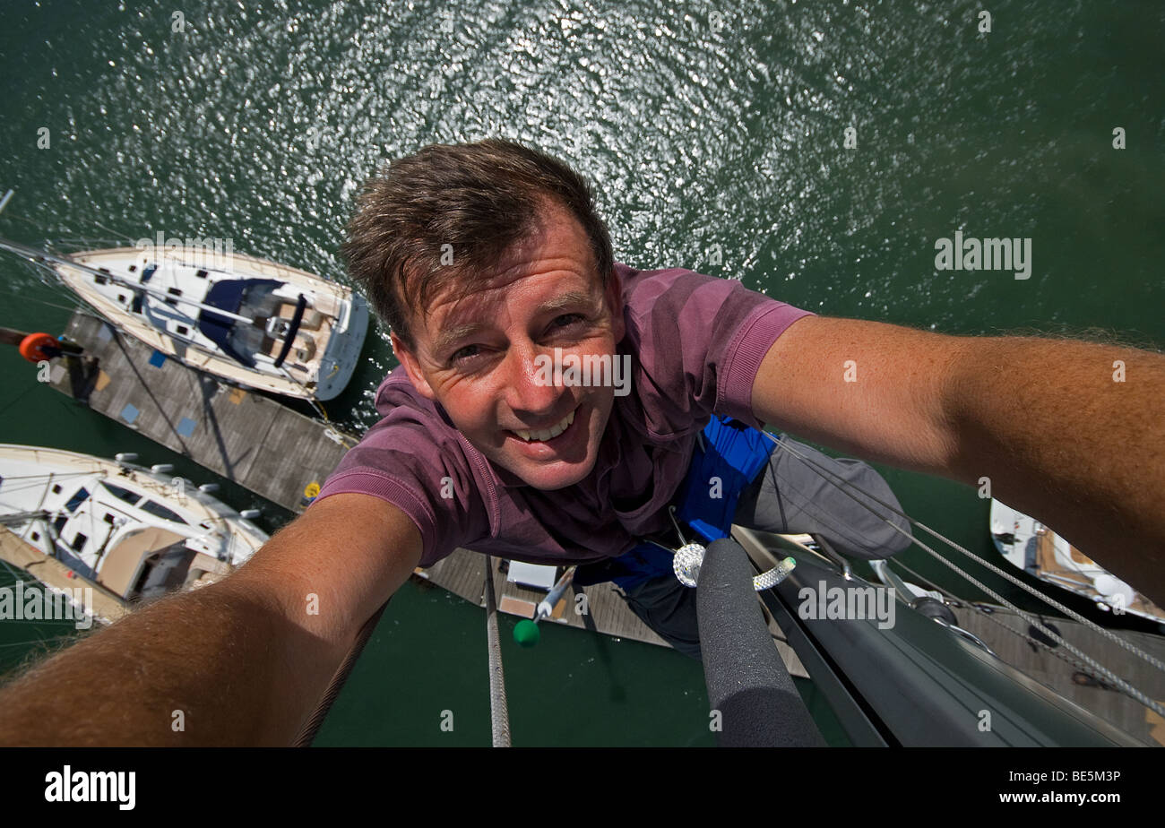 Neil Foster at the top of a Southerly 35 mast. - Stock Image