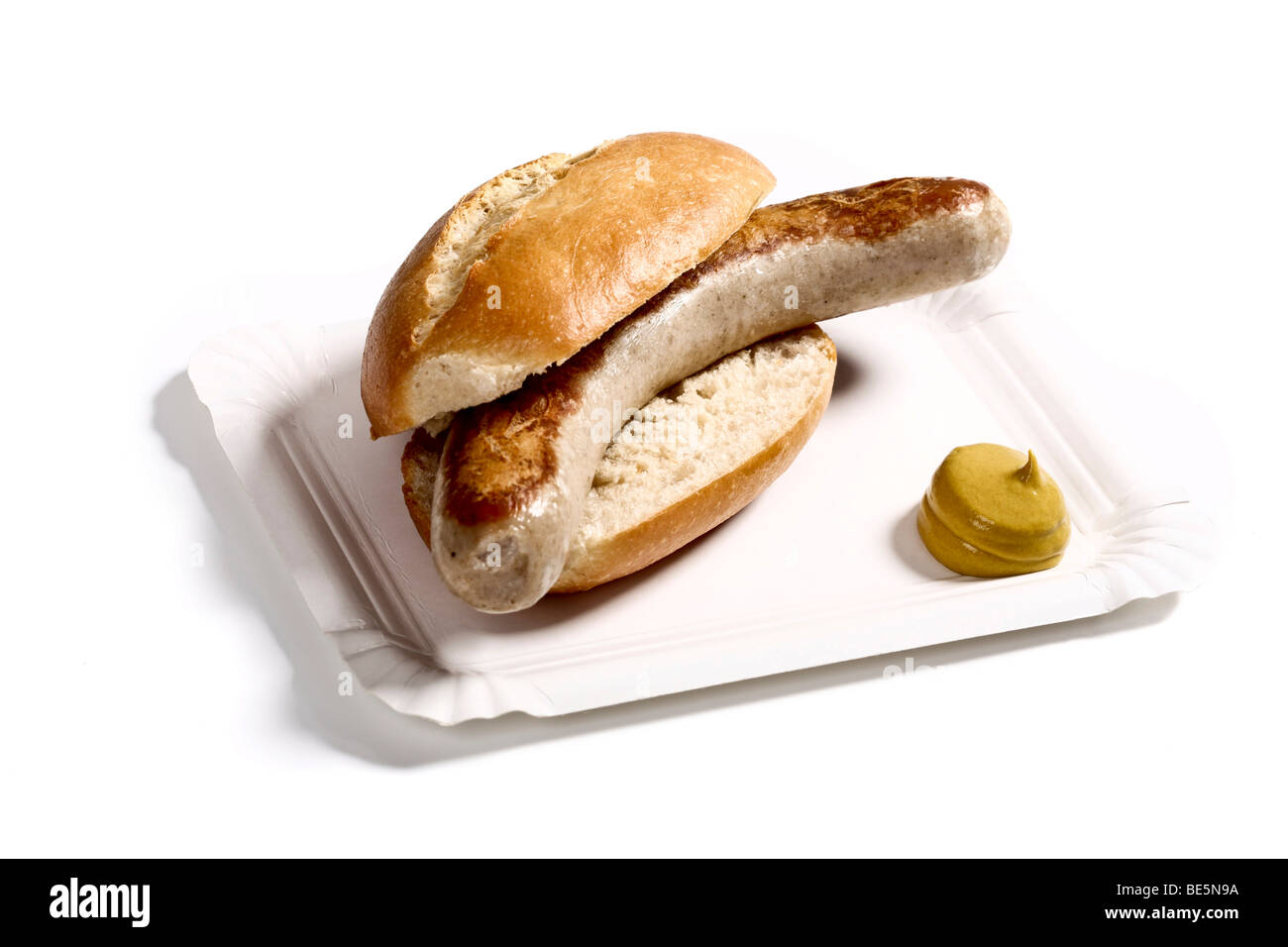 Bratwurst sausage in a bun with mustard on a paper plate Stock Photo