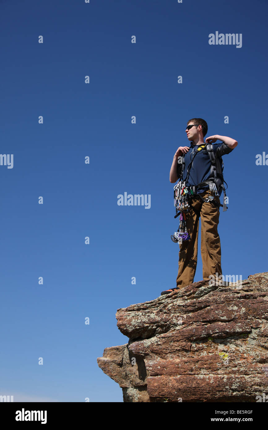 Rock climber stands on ledge - Stock Image