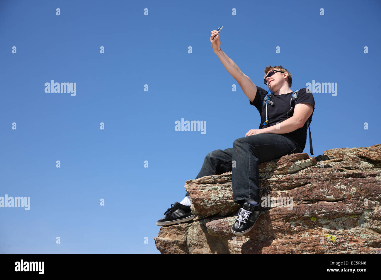 Young man taking self portrait on top of cliff - Stock Image