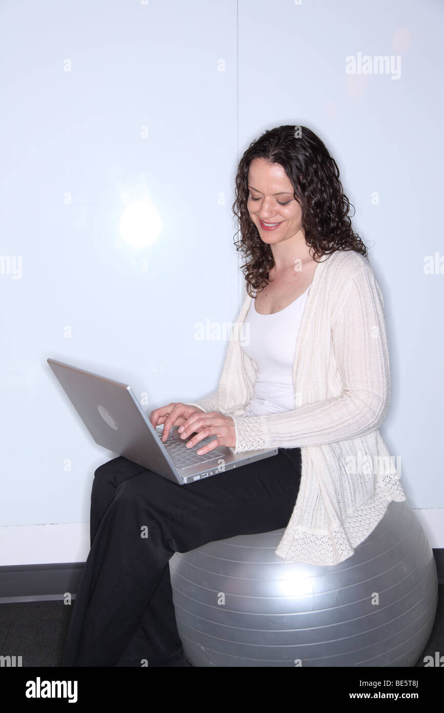 Woman sitting on exercise ball using laptop computer - Stock Image