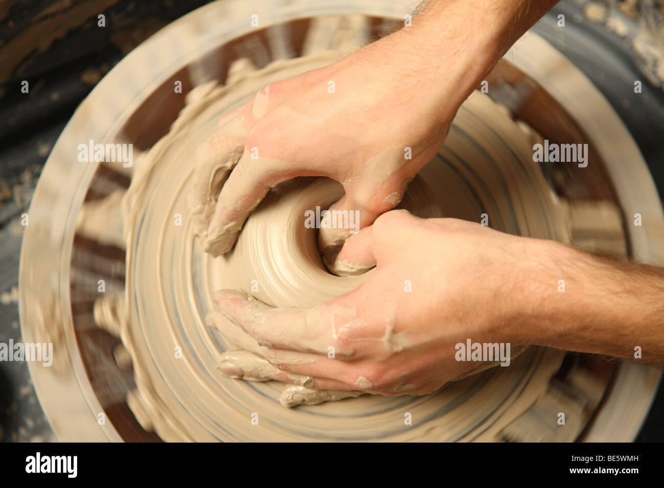 Closeup of hands working on pottery wheel - Stock Image