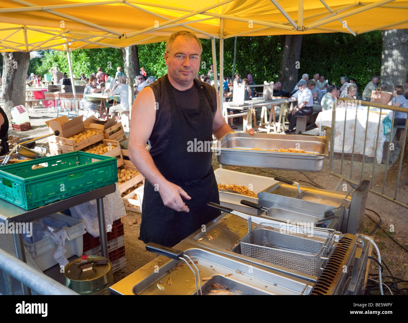 A stallkeeper making chips at a local farmers market, Laparade, Aquitaine, France - Stock Image