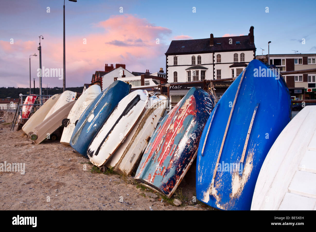 Early morning in Rhos harbour with the rowing boats stood up and tied to the harbour wall in Rhos on Sea, Colwyn - Stock Image