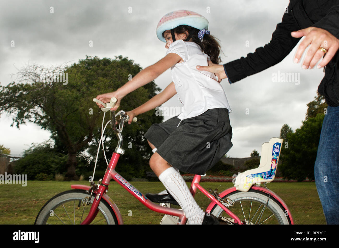 Parent helping child to learn riding a bicycle - Stock Image