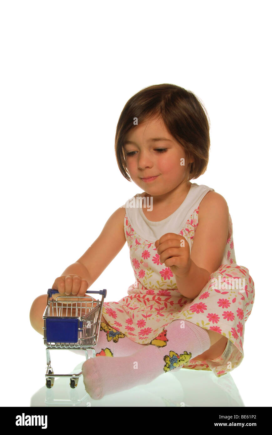Four-year-old girl with a cart, symbolic image for easy shopping - Stock Image