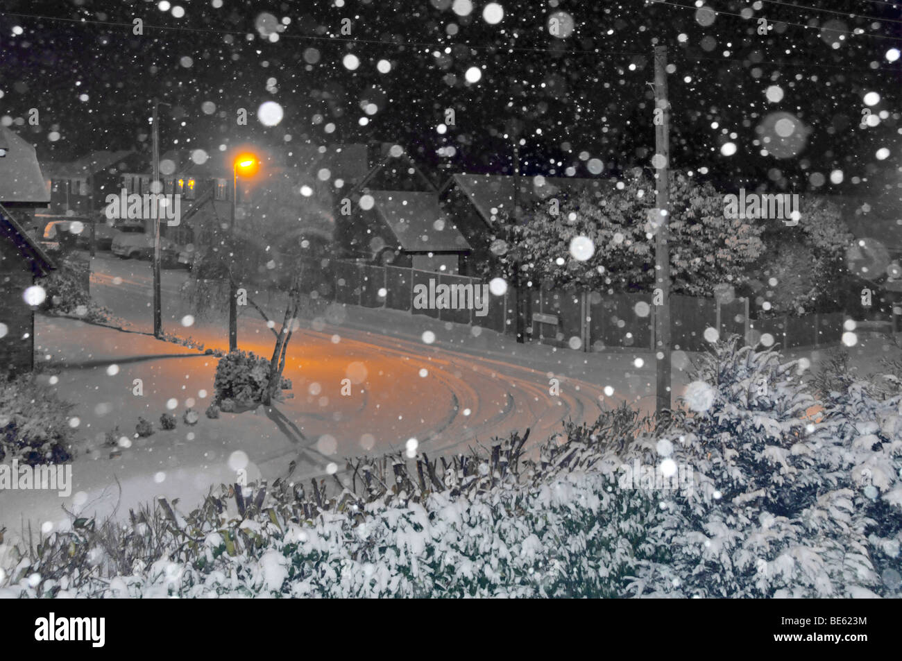 Snow flakes by flash with orange lighting illuminating snow covered street landscape manipulated Stock Photo
