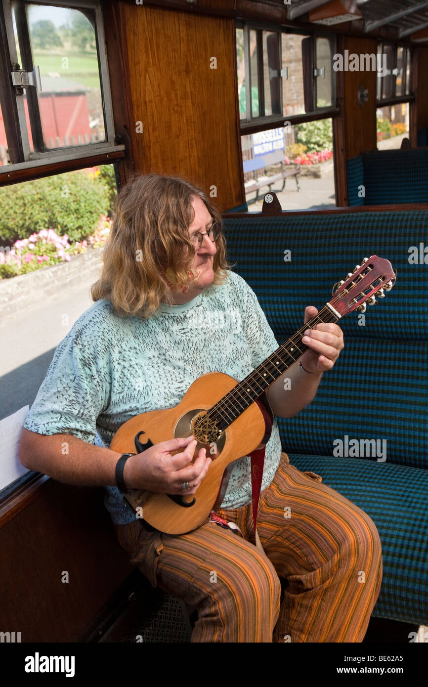 UK, England, Yorkshire, Keighley and Worth Valley Steam Railway, folk musician playing viola mandolin on train - Stock Image