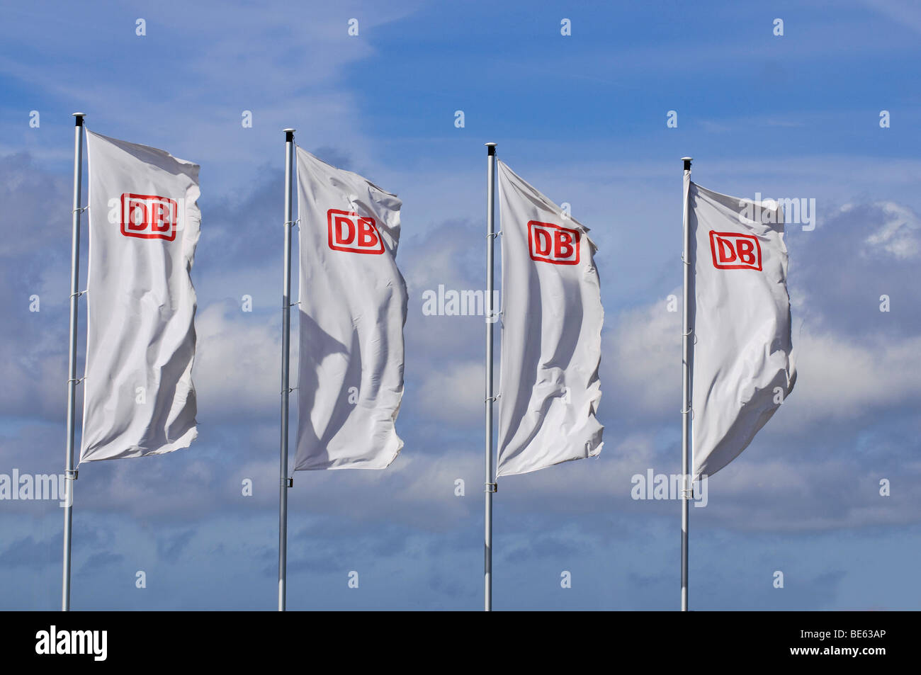 Four windblown white flags with the logo of DB, German Railways, in front of a sunny sky - Stock Image