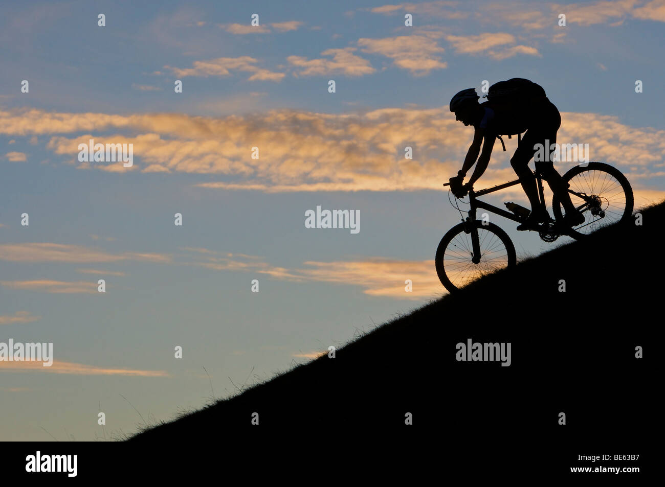 Mountainbiker, silhouette at Hohe Salve mountain in the evening light, Tyrol, Austria, Europe - Stock Image