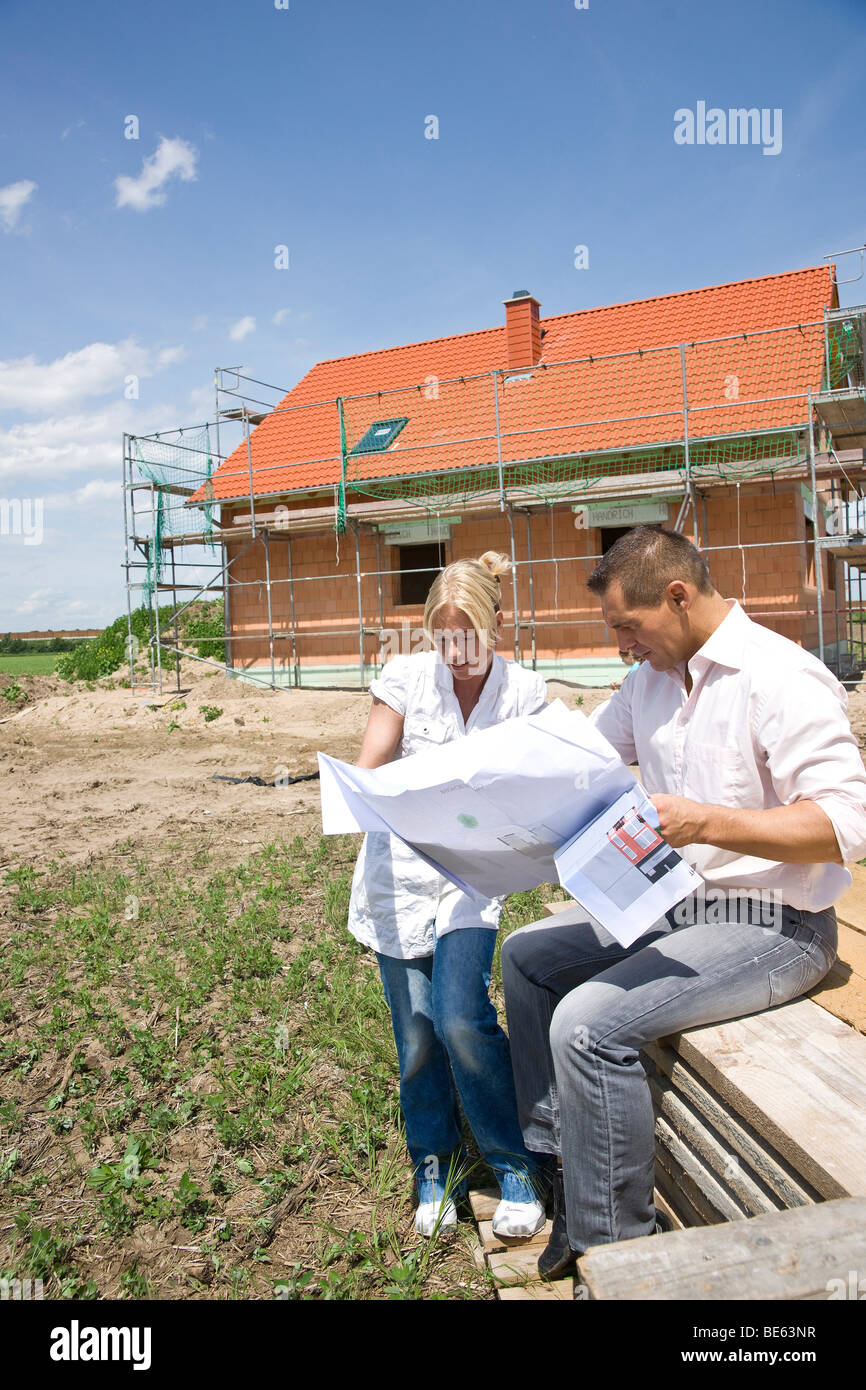Married couple discussing the construction plan in front of their future home Stock Photo