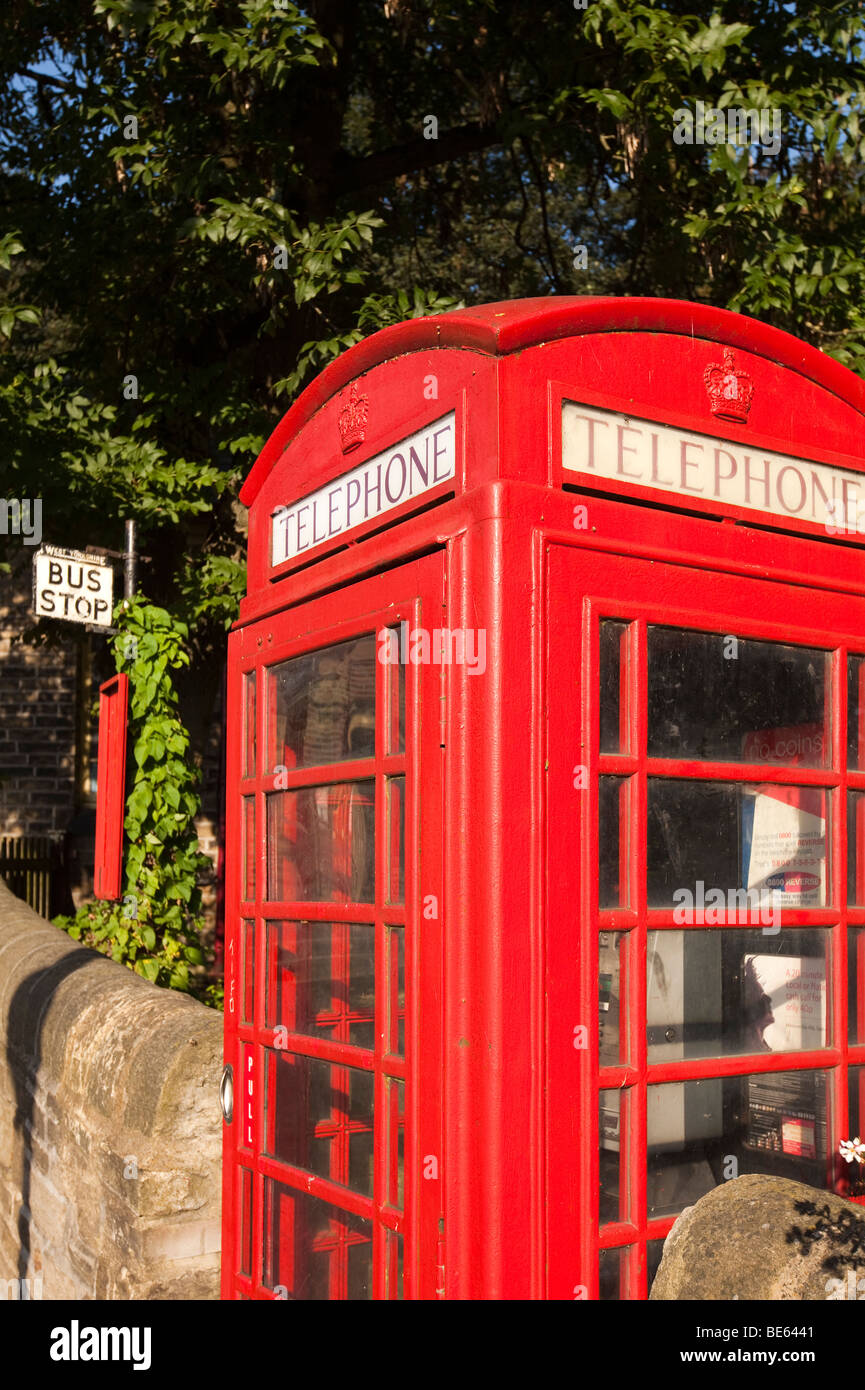 UK, England, Yorkshire, Haworth, old red K6 Phone box and bus stop outside railway station - Stock Image