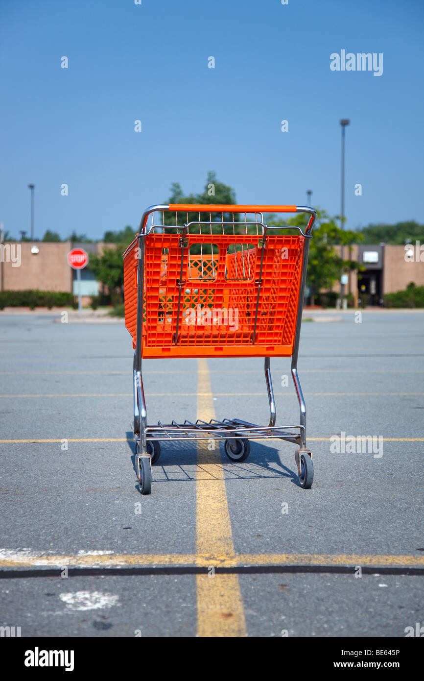 Vertical shot of an orange shopping cart isolated on a parking lot at the mall - Stock Image