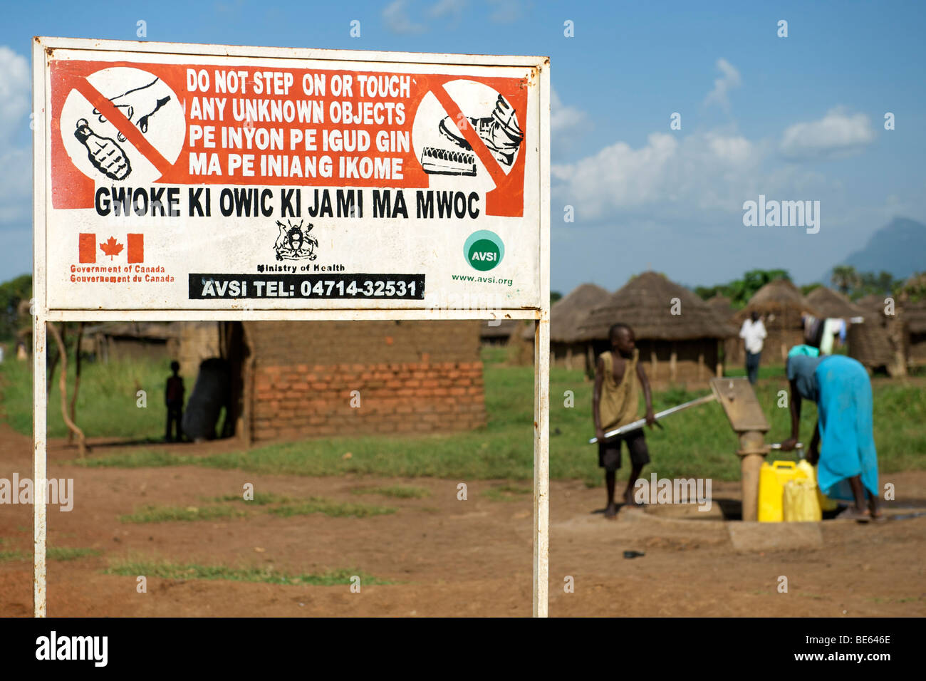 Villagers pumping water in front of a sign warning of unexploded ordnance in a village in the Kitgum region of northern - Stock Image