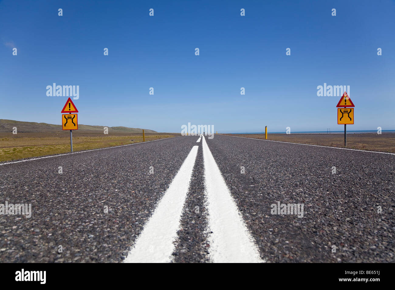 A ground level shot of a wide open road with warning signs - Stock Image