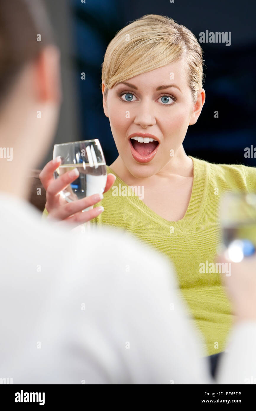 A beautiful young blond woman with a surprised look on her face while chatting with a friend over a drink - Stock Image