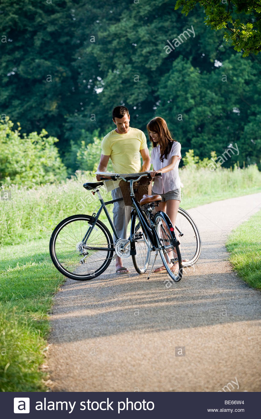 A young couple standing with bicycles holding a map Stock Photo