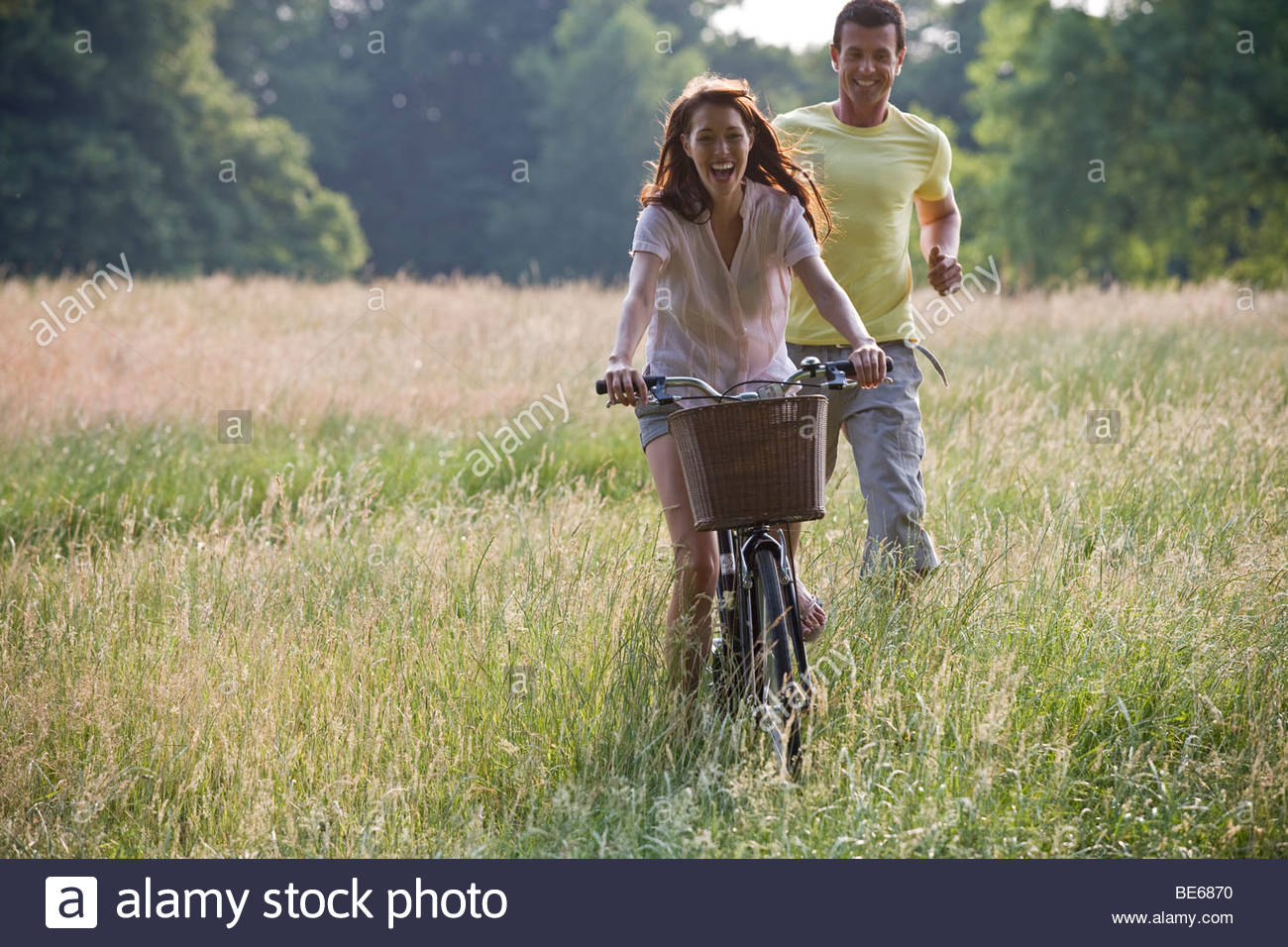 A young woman riding a bicycle through a field with her boyfriend running after her - Stock Image