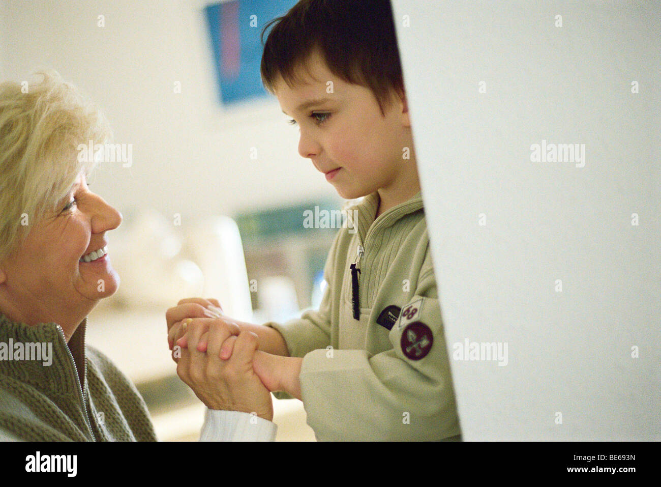 Little boy face to face with grandmother, holding hands - Stock Image