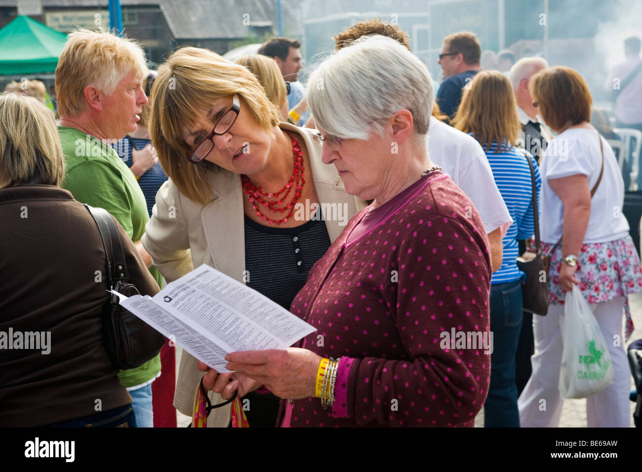 People reading leaflets at Abergavenny Food Festival Monmouthshire South Wales UK - Stock Image