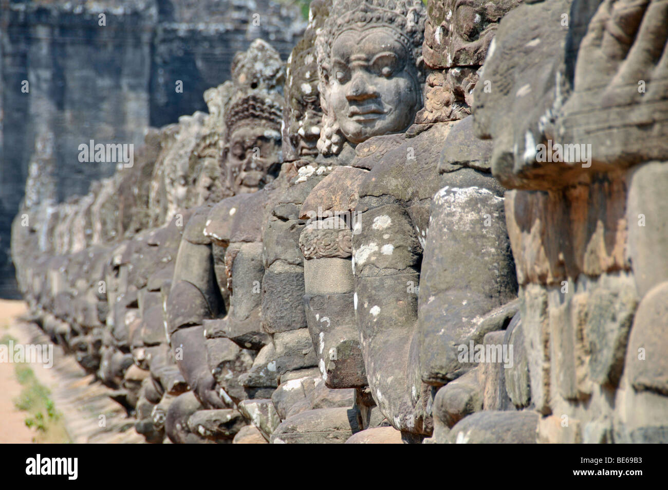 54 divine, fearsome stone creatures flanking the access to the entrance gates of Angkor Thom, Angkor Wat, Siem Reap, - Stock Image