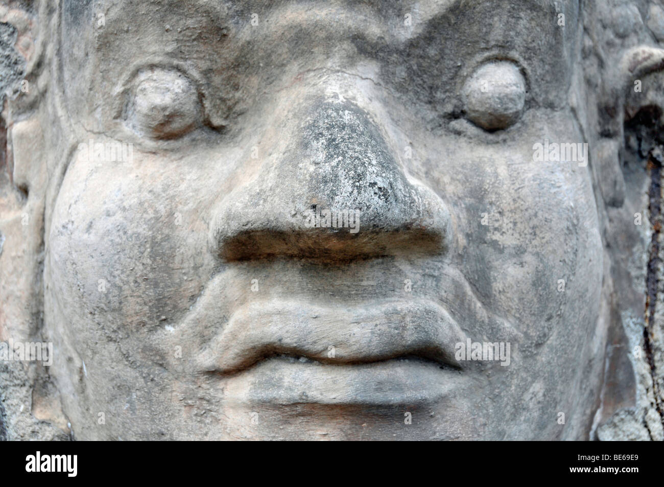 One of 54 divine, fearsome stone creatures flanking the access to the entrance gates of Angkor Thom, Angkor Wat, - Stock Image