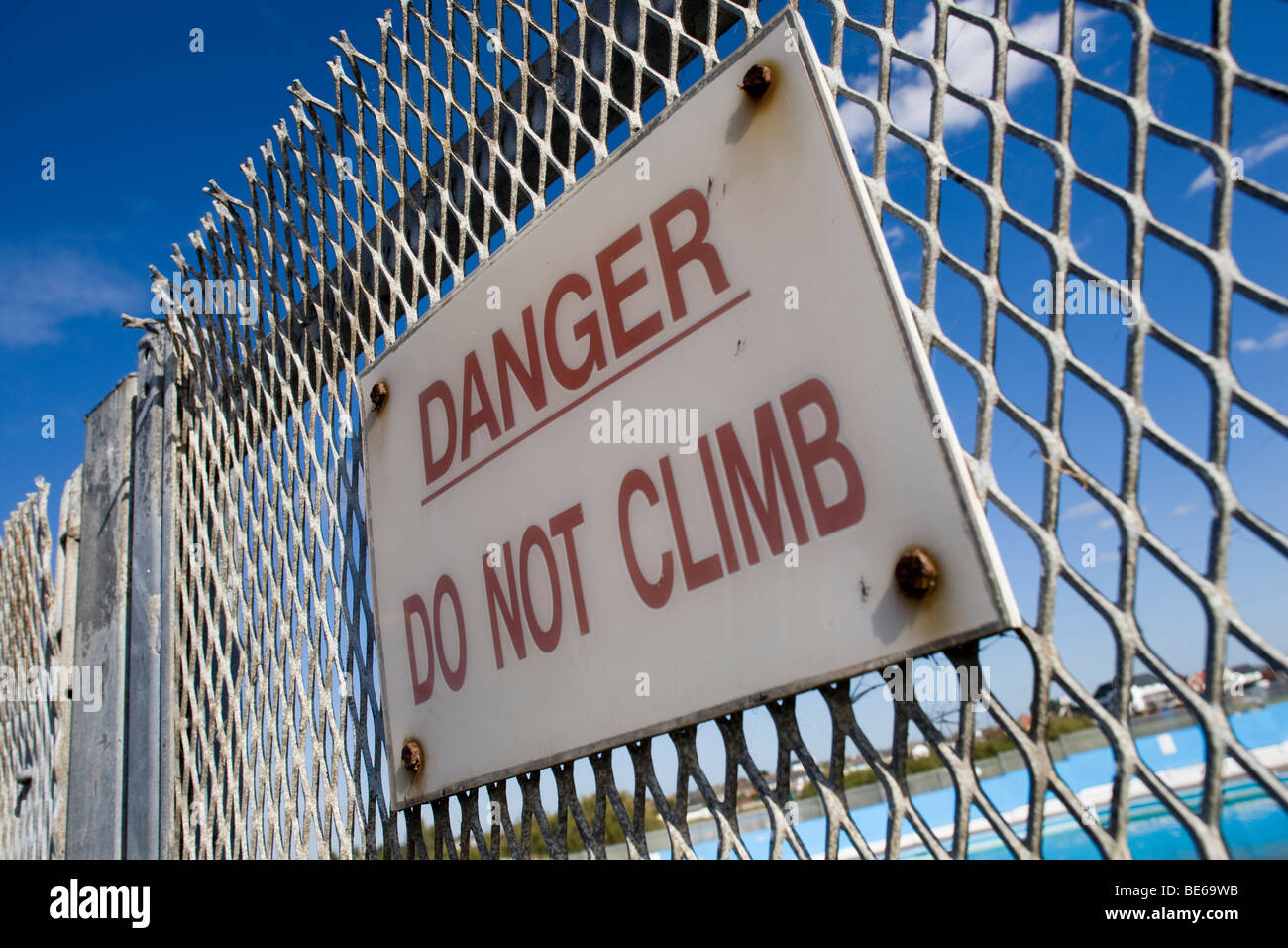 Danger Do Not Climb sign on the security fence around the closed outdoor swimming pool at Brightlingsea on the Essex - Stock Image