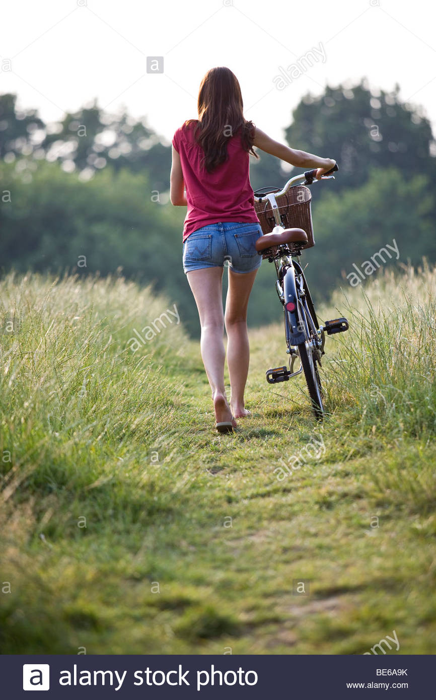 A young woman pushing a bicycle through a field - Stock Image
