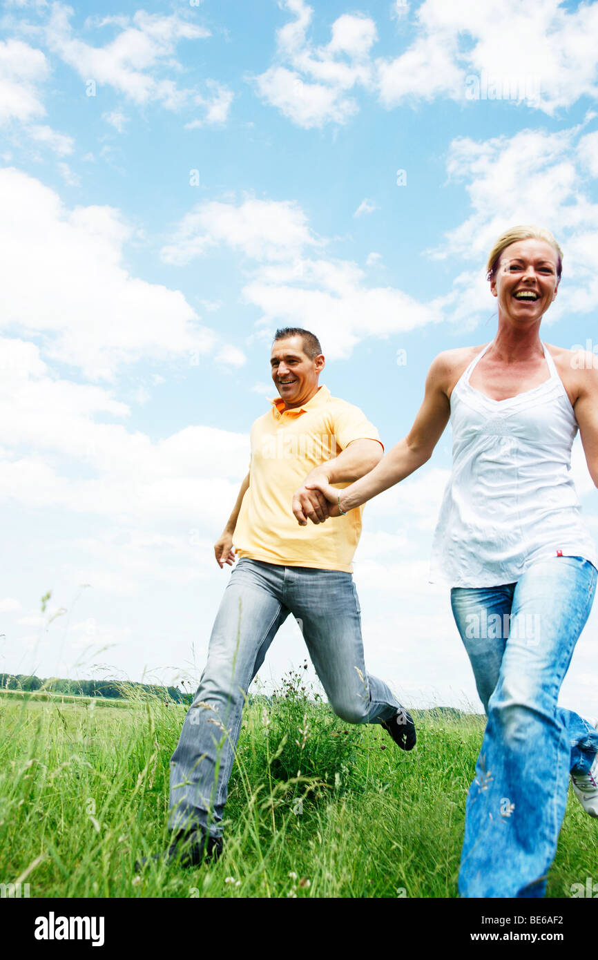 Couple running across a meadow, holding hands Stock Photo