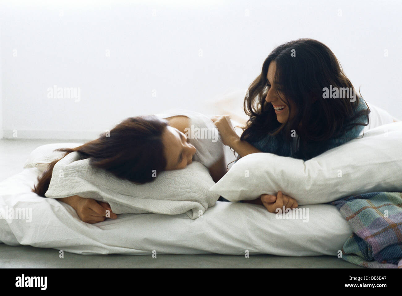 Female friends lying in bed together laughing - Stock Image