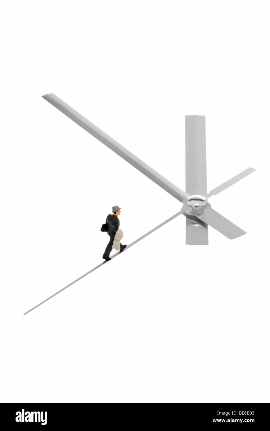 Business man running on second hand of a clock which shows five to twelve - Stock Image