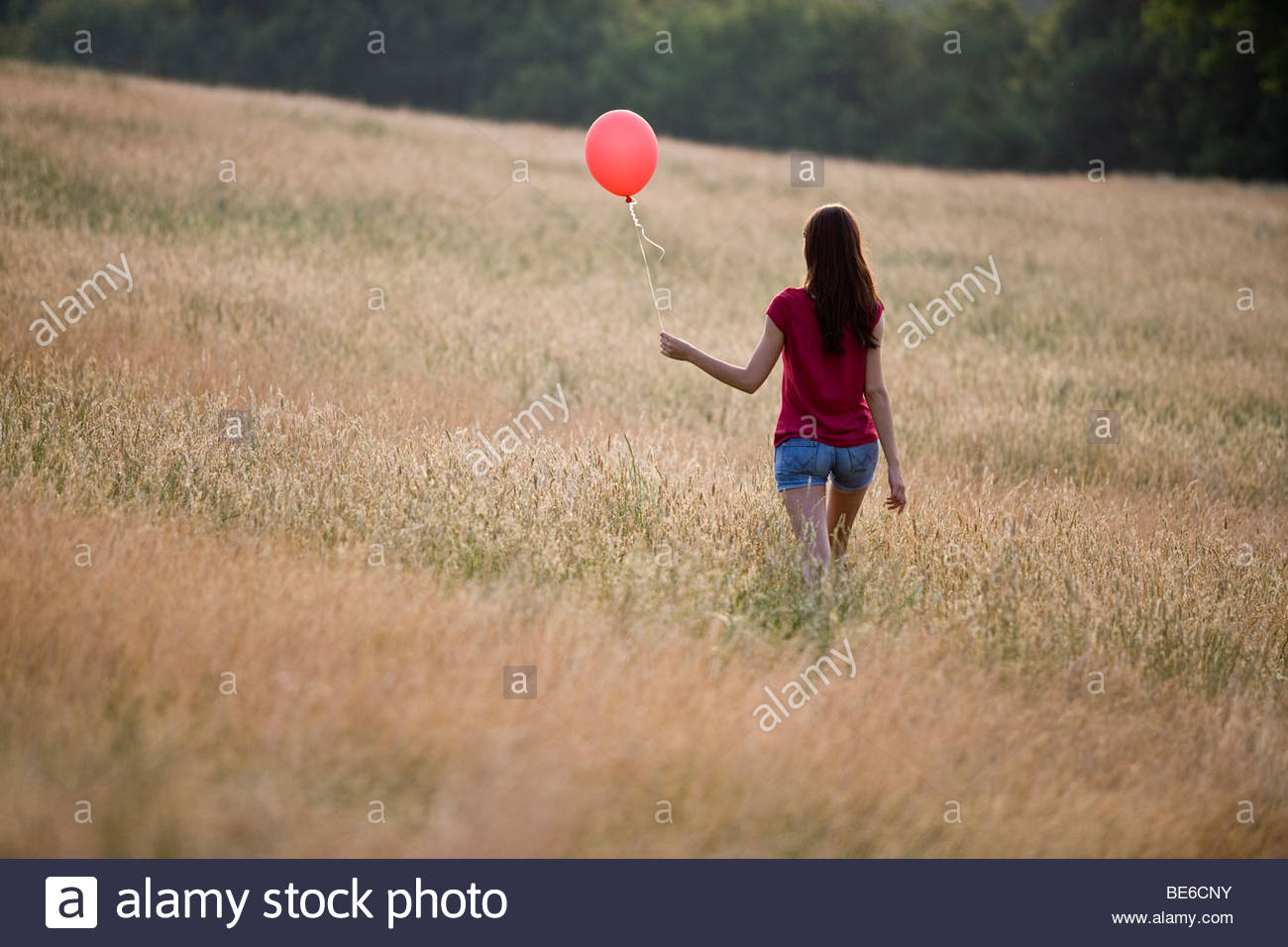 A young woman walking through long grass holding a red balloon - Stock Image