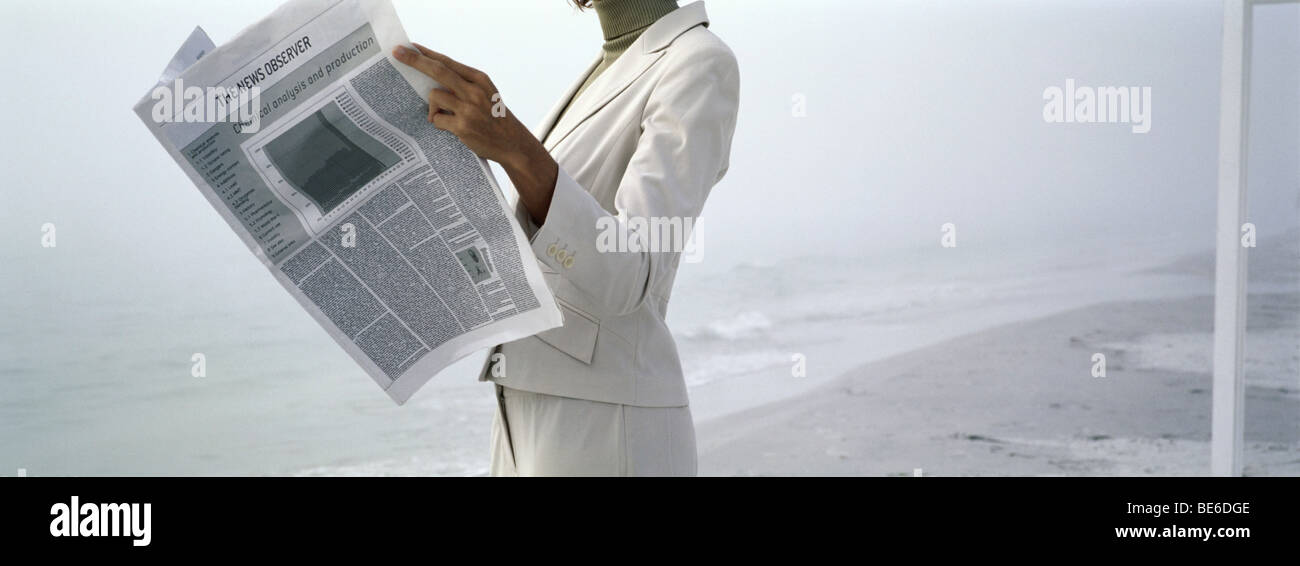 Woman in business attire reading newspaper on beach, cropped - Stock Image