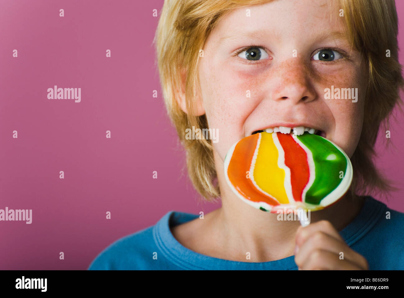 Boy eating lollipop, portrait - Stock Image