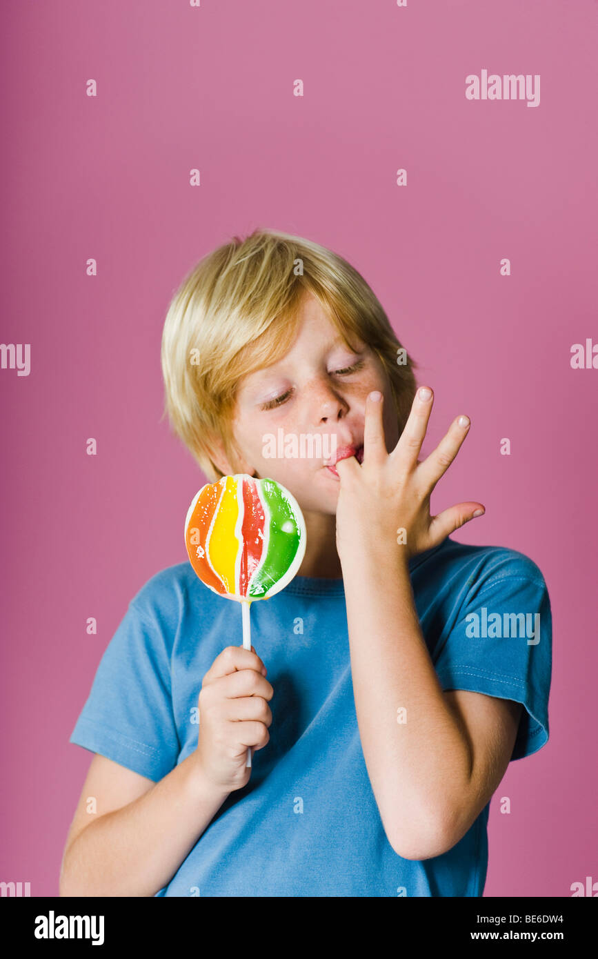 Boy with lollipop, licking fingers - Stock Image