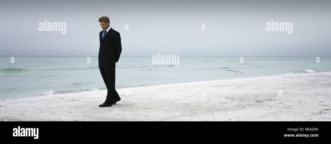 Man in suit walking on beach - Stock Image